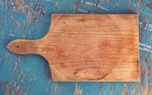 Постер, плакат: Cutting Board On Rustic Wooden Kitchen Table Top View