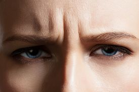 foto of wrinkled face  - Angry face of a young woman with facial wrinkles closeup - JPG