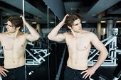Young Muscular Sexy Man Workout In Gym Near The Mirror Shadows poster