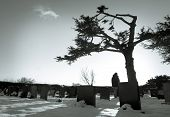 image of bereavement  - Lonely figure standing amongst tombstones in snowy cemetery - JPG