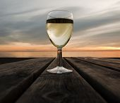image of beach sunset  - A glass of white wine at sunset next to the sea - JPG