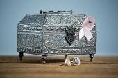 Surface level view of pink Breast Cancer Awareness ribbon with chest and rings on wooden table again poster