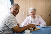 Smiling senior man playing chess with friend while sitting at table in nursing home poster