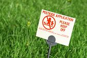 image of pesticide  - Pesticide warning sign on a bright green lawn - JPG