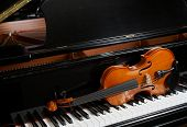 image of grand piano  - Violin on resting on keys of ebony grand piano - JPG