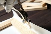 Stretching Canvas On Wooden Stretcher Bar, Canvas Pliers In A Hand poster