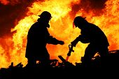 stock photo of fireman  - Silhouette of Firemen fighting a raging fire with huge flames of burning timber - JPG