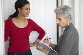stock photo of soliciting  - Black woman greeting a solicitor at her front door - JPG