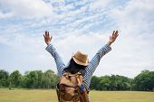 Happy Young Traveler Woman Backpacker Arms Up And Enjoying A Beautiful Of Nature At Grass Field Gree poster