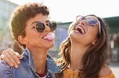 Young latin woman laughing while friend inflating bubble gum. Closeup face of multiethnic friends en poster