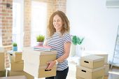 Middle age senior woman smiling happy holding cardboard boxes, packing moving to a new house poster