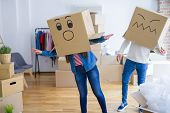 Crazy couple wearing boxes with funny faces over head, having fun happy for moving to a new house poster