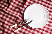 Empty White Plate, Fork And Knife On A Checkered Red Napkin, Top View. Image With Copy Space. Kitche poster