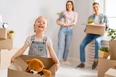 Happy young family are moving to new apartment. Parents and daughter with boxes. poster