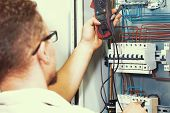 Electrician Measures Voltage With Multimeter In Electrical Cabinet. An Electrician Is Checking The V poster