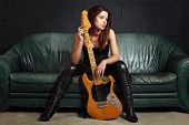 stock photo of lady boots  - Photo of a sexy female guitar player wearing leather boots and sitting on old leather couch - JPG