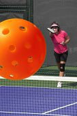 picture of pickleball  - Sports action image of a women serving a pickleball during a pickleball match - JPG
