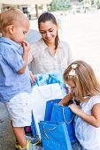 stock photo of curio  - Kids looking into shopping bags beside the mall - JPG