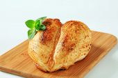 baked chicken breast on a wooden cutting board
