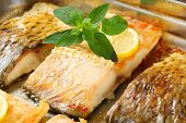 baked carp fillet with bones decorated with lemon and basil