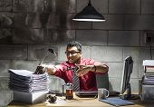 foto of indian money  - An image of an Indian businessman with a red shirt and tie behind a desk in a basement office - JPG