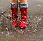 stock photo of wet  - Child wearing red rain boots jumping into a puddle - JPG