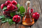 stock photo of wooden basket  - Apple cider vinegar in glass bottle and basket with fresh apples