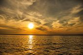 stock photo of wispy  - A sunset over the lake with grey wispy clouds - JPG