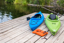 stock photo of bonaparte  - Two colorful kayaks and a life jacket rest on a fishing pier on a lake - JPG