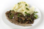 Fried and peppered escalope of veal served with mashed potatoes and a creamy sauteed mushroom sauce