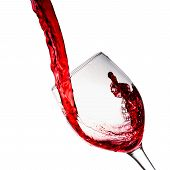 foto of squirting  - Red wine poured into wine glass on a white background - JPG