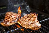 stock photo of red meat  - Beef steaks cooking in open flame on barbecue grill
