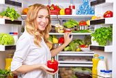 Woman chosen milk in opened refrigerator, cool new fridge full of tasty organic nutrition, female pr