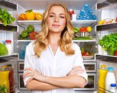 Portrait of cute serious female standing near open fridge full of healthy food, vegetables and fruit