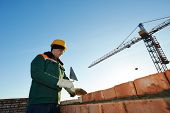 image of mason  - construction mason worker bricklayer installing red brick with trowel putty knife outdoors - JPG