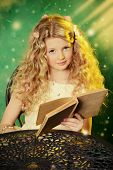 foto of loach  - Lovely girl in a lush white dress sitting at the table  over green background and reading a book - JPG