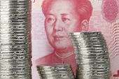 stock photo of yuan  - One yuan coins of chinese currency in front of a one hundread yuan bill