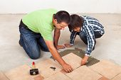 Man Laying Ceramic Floor Tiles Helped By His Son