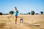 image of country girl  - Woman and dog running in country side dirt track - JPG