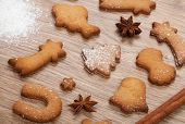 Gingerbread cookies with spices and flour over wooden table