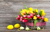stock photo of wooden basket  - spring tulips in wooden basket with Easter eggs on wooden background - JPG