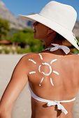foto of sun tan lotion  - Tanning lotion in the shape of sun on woman - JPG