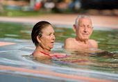 stock photo of hot couple  - Senior couple enjoying holiday in the pool with hot water