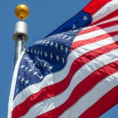 picture of flag pole  - Close-up American flag blows in the wind with flag pole focus on star of waving flag