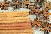 stock photo of ouzo  - Anise stars and cinnamon sticks on flax background - JPG