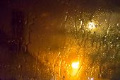foto of diffusion  - Rain on a glass window at night during a storm. Diffused light from street lights.