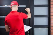 image of red back  - Back view of a delivery man knocking on the client