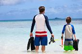 pic of fin  - Back view of father and son with snorkeling equipment fins and mask at tropical beach - JPG
