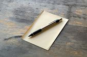 image of manila paper  - A silver and black mechanical pencil on a sheet of yellow manila paper on a distressed wooden table - JPG