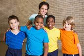 stock photo of physical education  - Cute pupils smiling at camera with PE teacher at the elementary school - JPG